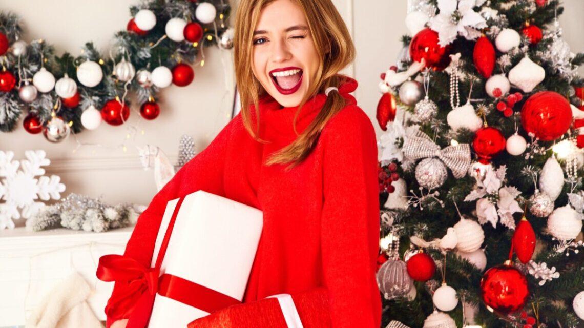 Chica sonríe delante del arbol de Navidad